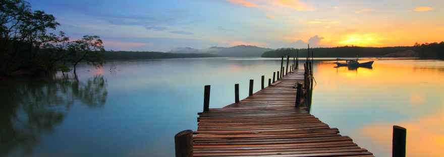 wooden pier stretching across water at sunset
