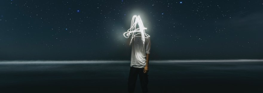 person standing in desert, using light to draw the letter A on long exposure photograph