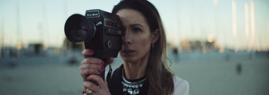 woman looking through film camera