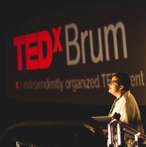 helga henry standing at podium, presenting at ted x brum
