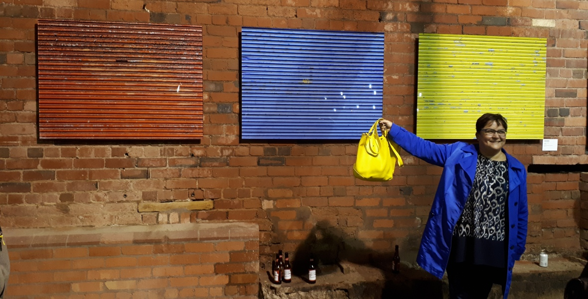 helga henry stands in front of a wall with three panels in red, blue, and yellow, she is smiling as her clothes match the wall