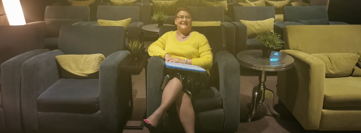helga henry, smiling, wearing a yellow jumper, sits in an empty auditorium with large armchair style seats in yellow and grey