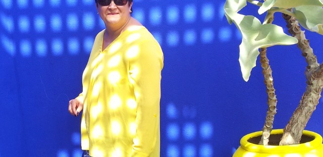 Woman in yellow top and blue trousers by a blue wall and yellow plant pot