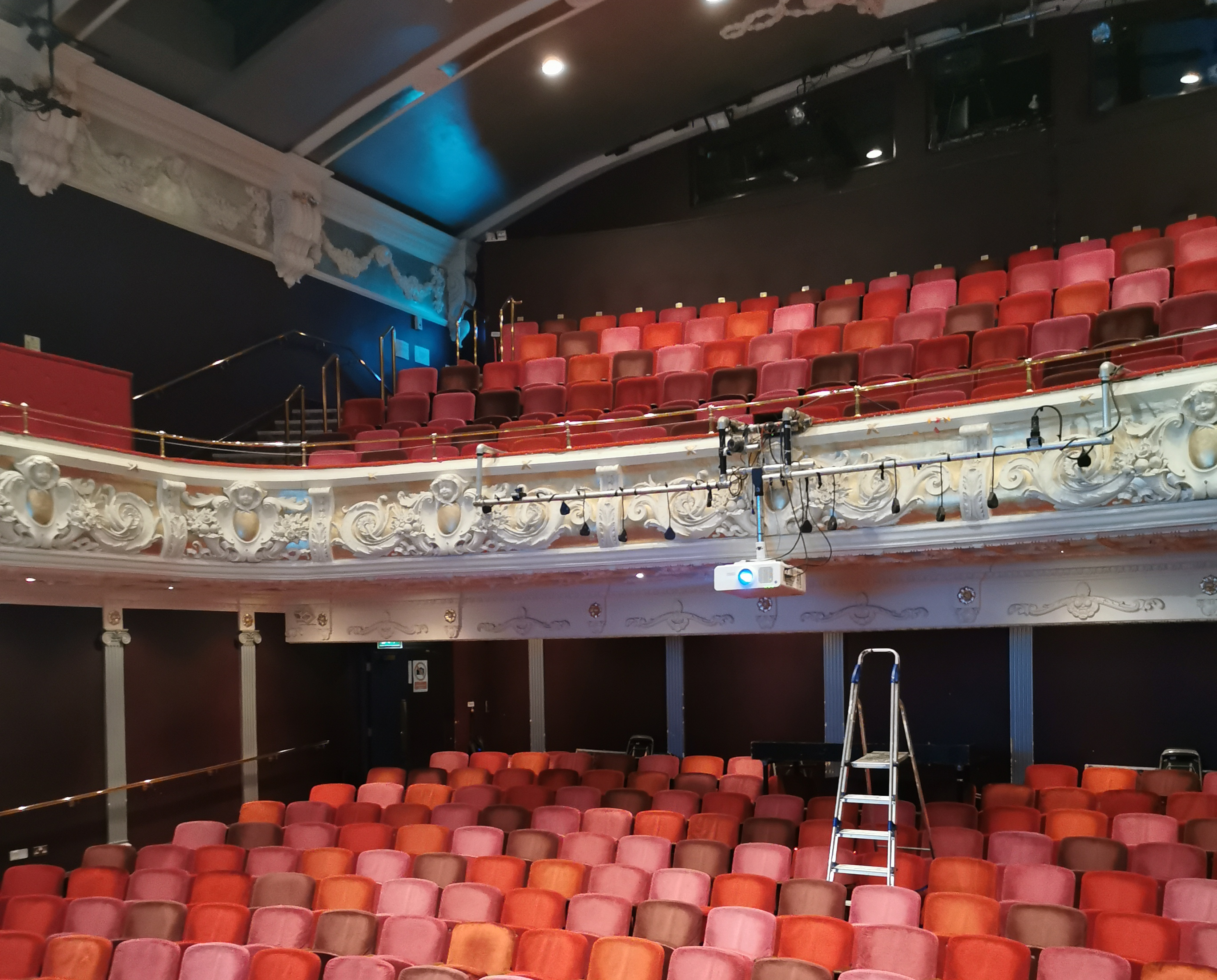 an empty theatre auditorium with rows of read seats and a balcony, a ladder in the centre of the room